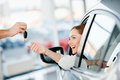 Seller giving key to happy young woman sitting in new car Royalty Free Stock Photo