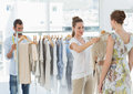 Seller helping shopper choose clothes in store female the the Stock Photo