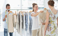 Seller helping shopper choose clothes in store female the the Stock Image
