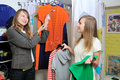 Seller offers to a girl a blouse Royalty Free Stock Photo