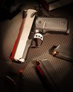 Semi automatic handgun stainless that has red lighting and magazines nearby Royalty Free Stock Photography