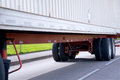 Semi trailer wheelbase chassis frame with trailer axles wheels and on orange of long commercial truck mounted a ribbed container Stock Photography