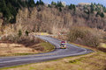Semi truck Rig on winding road with winter trees Royalty Free Stock Photo
