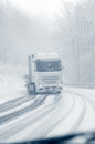 Semi truck on a snowy mountain road modern with heavy loaded trailer trying to climb curvy just minutes after rain changed to Royalty Free Stock Image