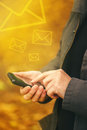 Sending SMS messages on mobile phone in autumn Royalty Free Stock Photo