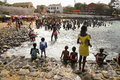 Senegal children play in sea by rocky beach Stock Image