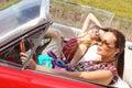 Senhoras bonitas com os vidros de sol que levantam em um carro do vintage em um verão da mola do dia ensolarado Fotos de Stock Royalty Free