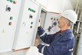 Senior adult electrician engineer worker builder testing equipment in fuse box Stock Photo