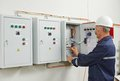 Senior adult electrician engineer worker builder testing equipment in fuse box Stock Images