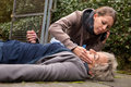 Senior adult had an collapse a young women do first aid Royalty Free Stock Photography