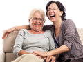 Senior adult two women laughing portrait old mother and daughter sitting on the sofa very happy family isolated on white Stock Images