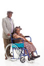 Senior african man wife wheelchair loving men pushing his on isolated on white Stock Photography