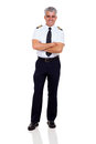 Senior airline captain portrait of with arms folded isolated on white Royalty Free Stock Photography
