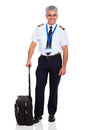 Senior airline pilot wearing uniform standing next to briefcase Stock Images