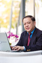 Senior Asian businessman in suit using laptop PC Royalty Free Stock Photo