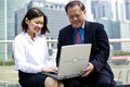 Senior asian businessman and young female asian executive using laptop pc outdoor Royalty Free Stock Photo