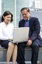 Senior asian businessman and young female asian executive using laptop pc outdoor Royalty Free Stock Photos
