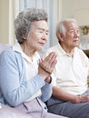 Senior asian couple praying Royalty Free Stock Photos