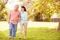 Senior Asian Couple Walking Through Park Together Royalty Free Stock Photo