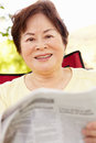 Senior Asian woman reading outdoors Royalty Free Stock Photo