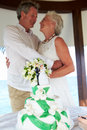 Senior beach wedding ceremony with cake in foreground Stock Image