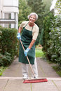 Senior with broom Royalty Free Stock Images