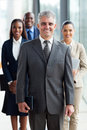 Senior business leader cheerful standing in front of his team in office Stock Photography