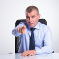 Senior business man at desk points at you bussines sitting bureau and pointing and looking the camera on gray background Royalty Free Stock Images