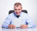 Senior business man smiles at his tablet bussines holding and looking while the office with a smile on face on gray background Royalty Free Stock Image