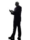 Senior business man on the telephone text messaging silhouette Stock Images