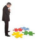 Senior businessman assembling a jigsaw puzzle Stock Image