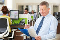 Senior Businessman In Busy Modern Office Royalty Free Stock Photo