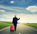 Senior businessman hitch hiking on the road back view of Stock Image