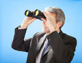 Senior businessman looking through binoculars Royalty Free Stock Photos