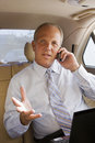 Senior businessman sitting in back seat of car using mobile phone gesturing with hand portrait Royalty Free Stock Image