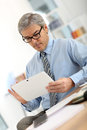 Senior businessman using tablet in office working on Royalty Free Stock Images