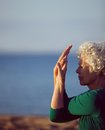 Senior caucasian woman exercising by the sea old stretching her arms on beach in morning fitness and healthy lifestyle Stock Photography