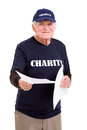 Senior charity worker happy handing out papers Stock Photo