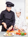 Senior chef teaches young chef to properly cut Stock Photos
