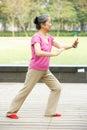 Senior Chinese Woman Doing Tai Chi In Park Stock Photos