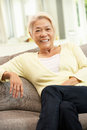 Senior Chinese Woman Relaxing On Sofa At Home Royalty Free Stock Photography