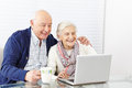 Senior citizen couple using happy laptop computer at home Stock Image