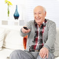 Senior citizen man watching tv happy with remote control Stock Images