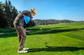 Senior citizen is playing golf active retirement a man golfing to stay in shape on green grass with woods in the background Stock Images
