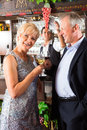 Senior couple at bar with glass of wine in hand Stock Photo