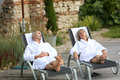 Senior couple with bathrobe relaxing on wood deck in spa hotel in long chairs Royalty Free Stock Image