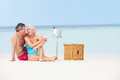 Senior couple on beach with luxury champagne picnic smiling Stock Photos