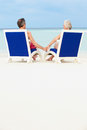 Senior couple on beach relaxing in chairs holding hands Royalty Free Stock Images