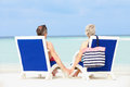 Senior couple on beach relaxing in chairs holding hands Stock Photo