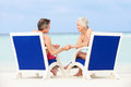Senior couple on beach relaxing in chairs smiling Royalty Free Stock Image